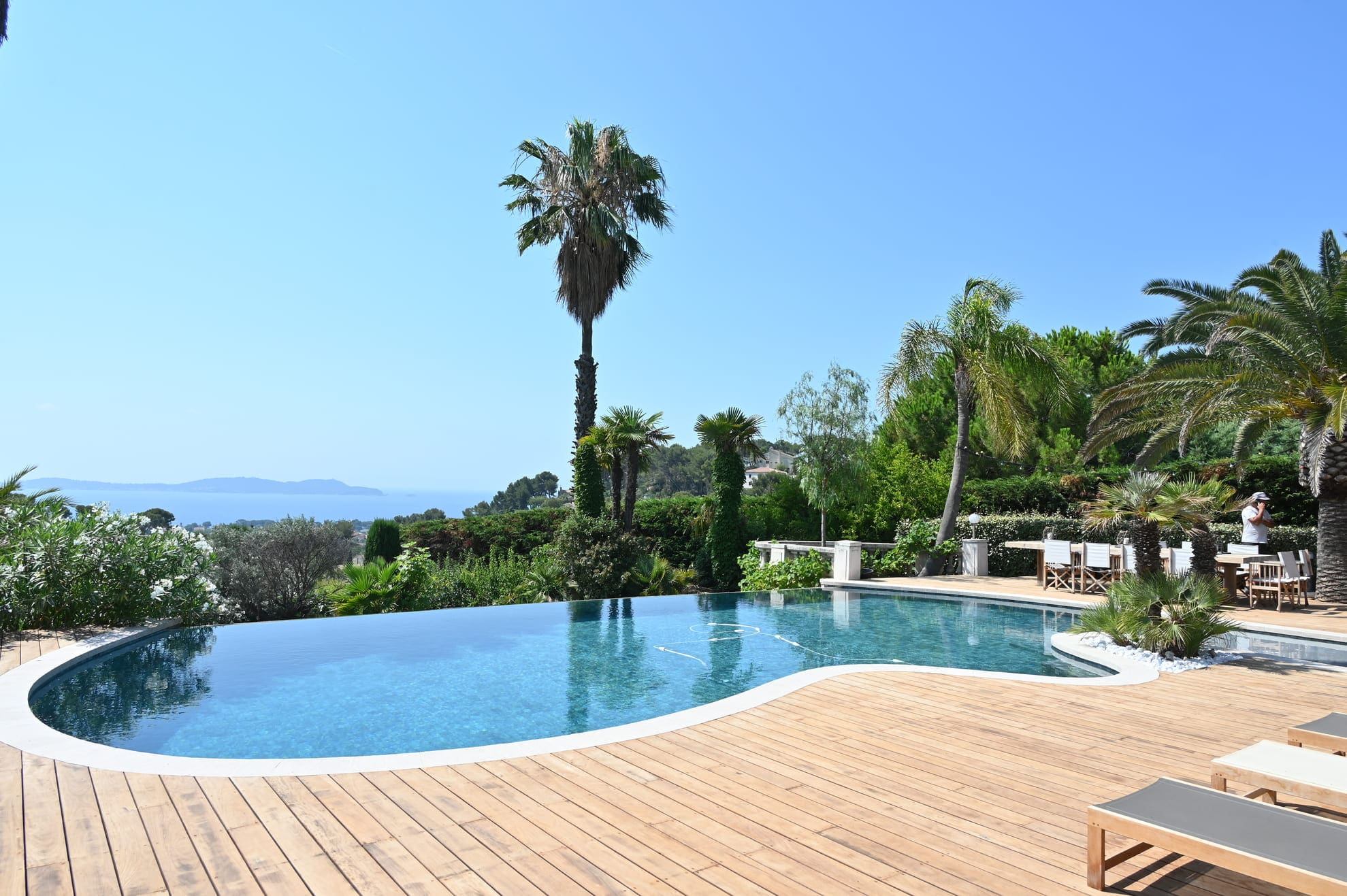 Une piscine à débordement avec une terrasse en bois
